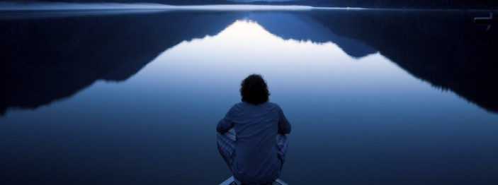 Person sitting at the edge of a lake