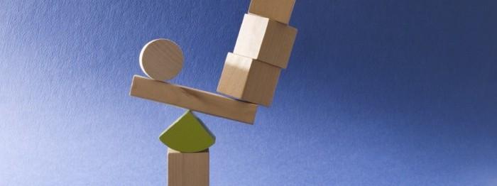 Wood blocks precariously balancing on a pie-shape block