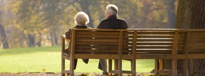 Old couple sitting on a park bench, facing away