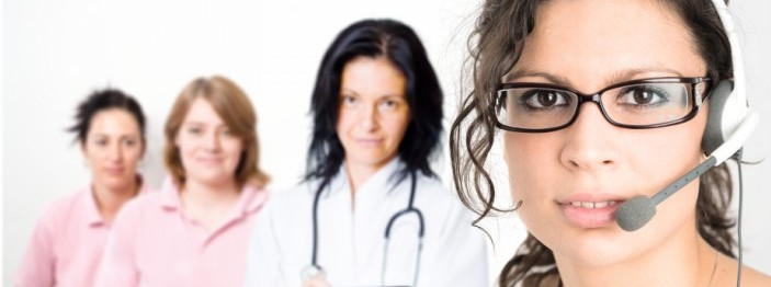 Woman wearing a headset with three other women out of focus behind her.