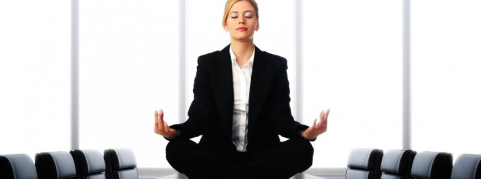 Woman in a meditative pose sitting on a conference room table