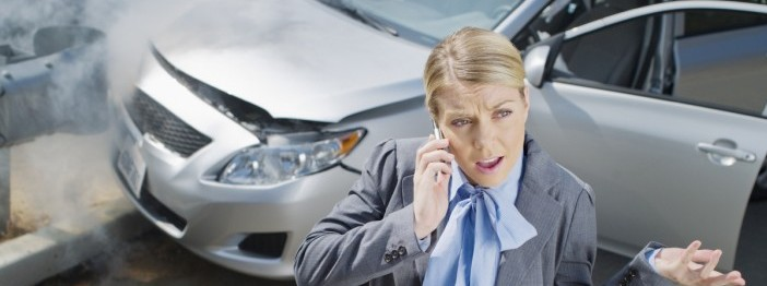 Distressed woman speaking on her cellphone next to a crashed car.