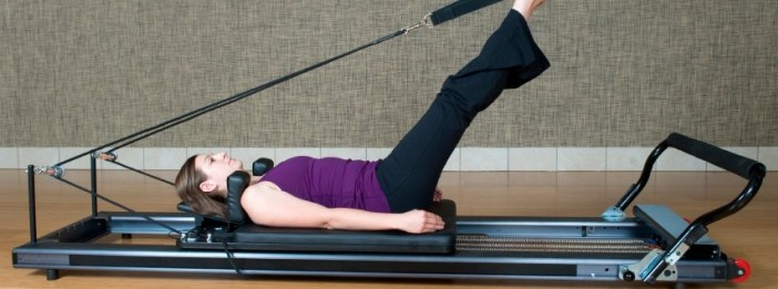 Woman doing exercise on a Pilates machine